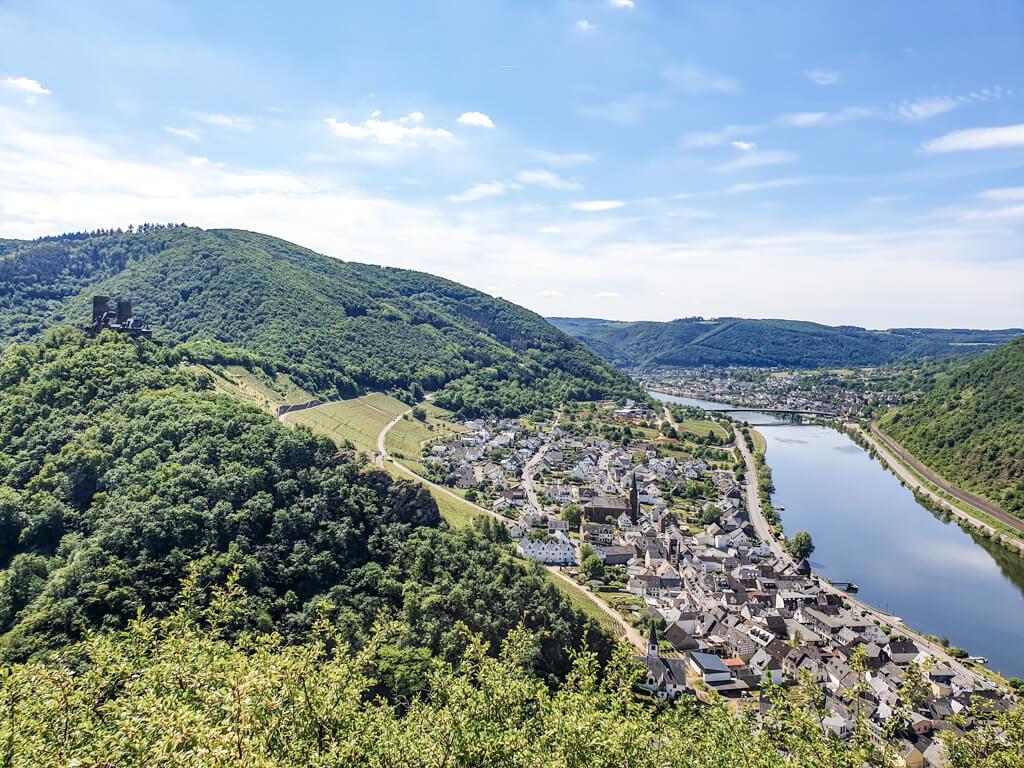 Ausblick auf grüne Hügel mit einer Burg, darunter liegen rechts ein kleiner Ort und die Mosel