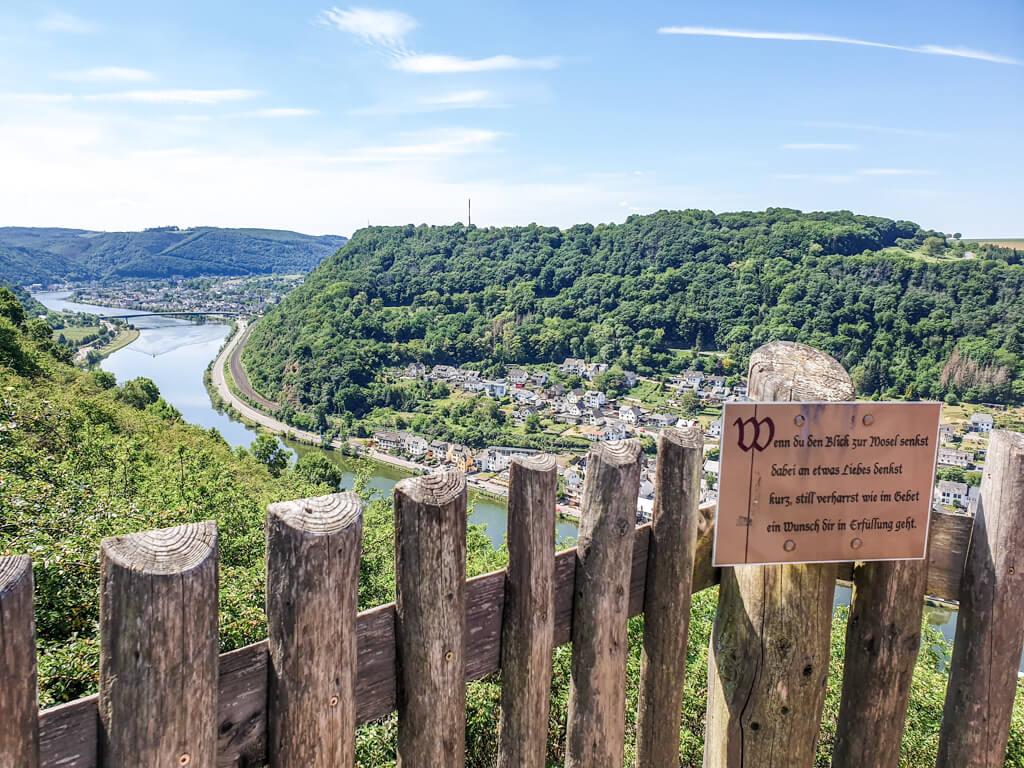 Aussichtsplattform mit Holzgeländer und Blick auf die Mosel sowie grüne Hänge darunter