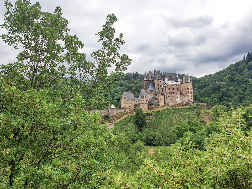Burg Eltz inmitten von grünen Wäldern - Blick vom Moselsteig aus