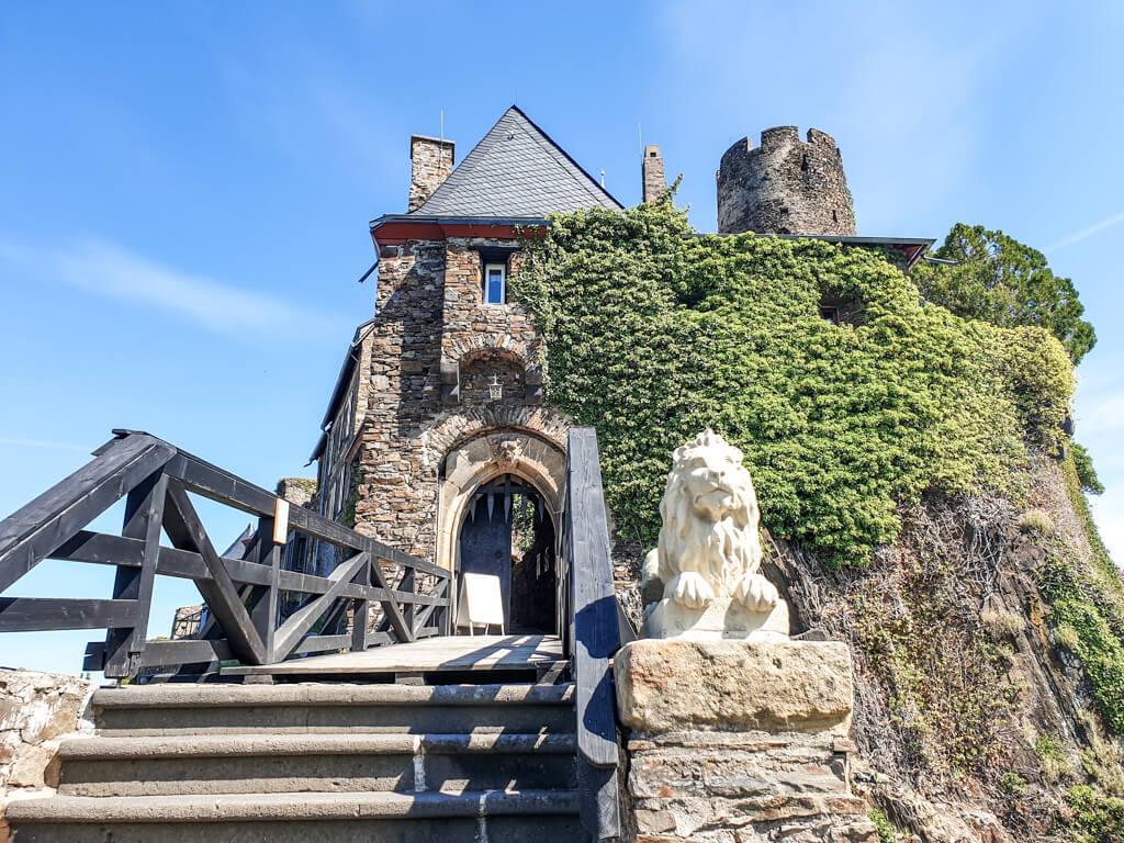 Treppe mit Holzgeländer führt zu einem Eingangstor der Burg Thurant; neben der Treppe ein steinerner Löwe