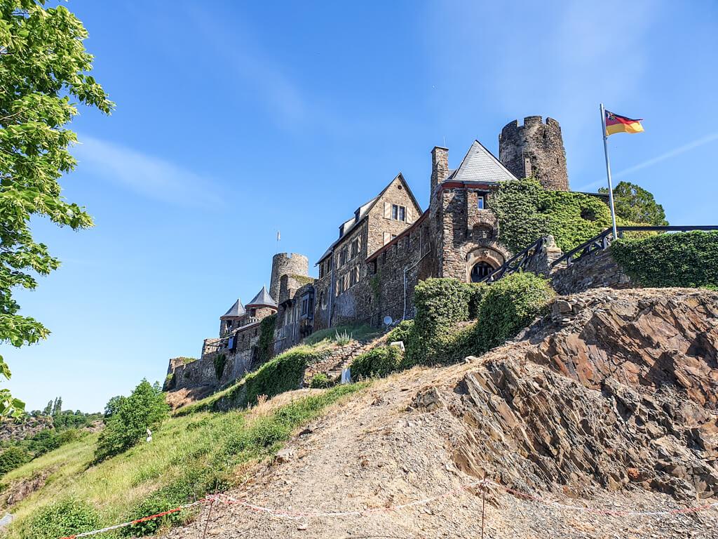 Burganlage mit mehreren Türmen auf einem Hügel im Grünen