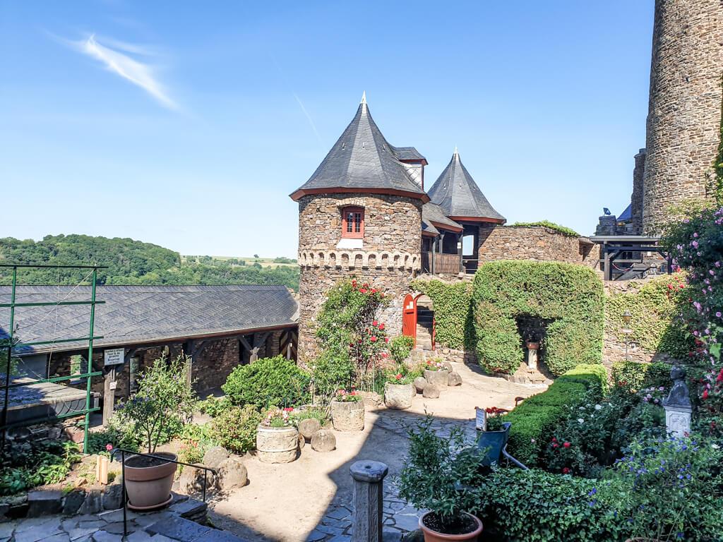 Innenhof der Burg Thurant mit Ecktürmen und Pflanzen an einem Weg