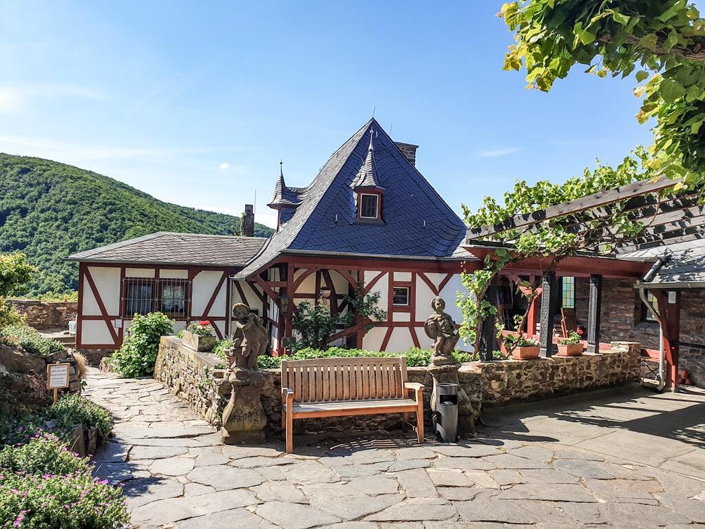 Fachwerkhäuschen in einem gepflasterten Hof der Burg Thurant