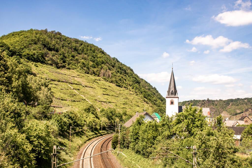 kleiner Kirchturm inmitten von grünen Hügeln