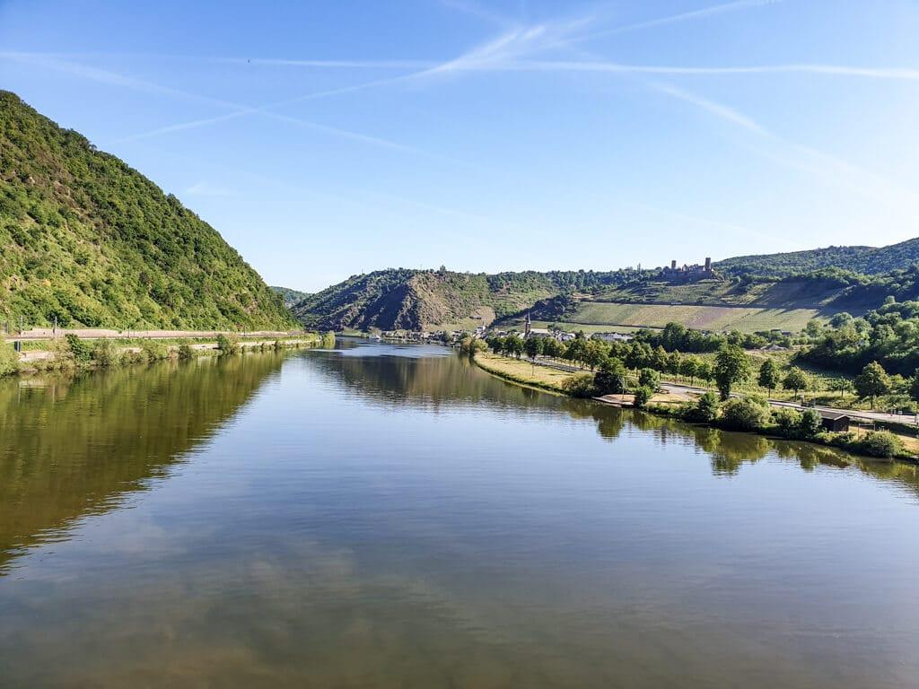 breiter Fluss in der Mitte des Bildes, zu beiden Seiten ein kleiner Weg am Ufer und bewaldete Hänge