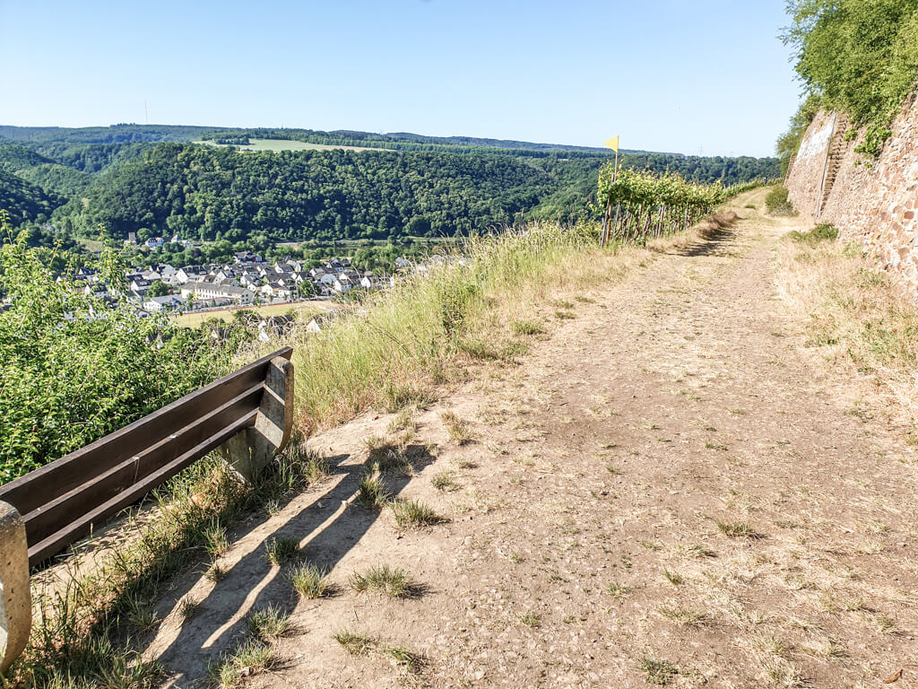 Wanderweg in den Weinbergen mit einer Bank und Blick auf den Ort Winningen