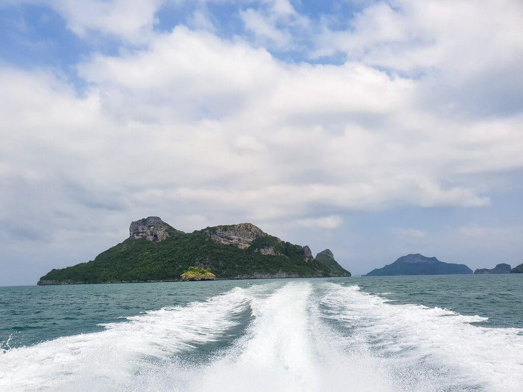aufgeschäumtes Wasser von einem Boot auf dem Meer - Blick auf eine felsige Insel