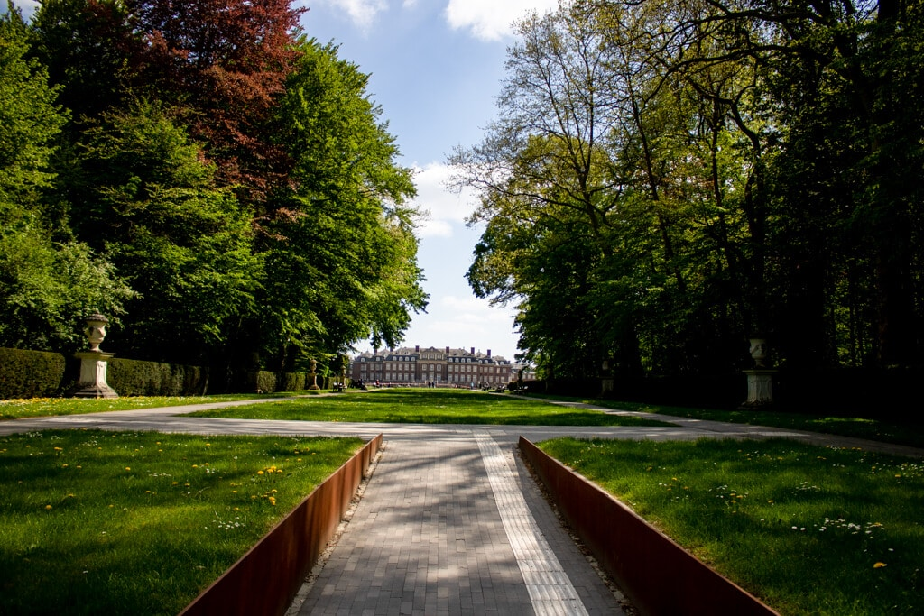 Blick auf das Schloss Nordkirchen in der Ferne, davor ein gerader Weg gesäumt von Bäumen