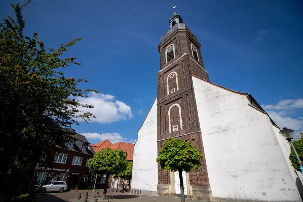 Kirche mit geklinkertem Glockenturm und weißem Seitenschiff