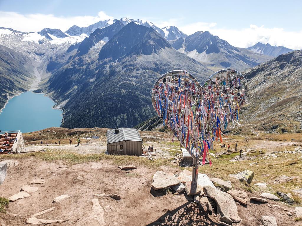 Herz aus Metall mit bunten Fähnchen steht auf einem Berg, der zu einem blauen Bergsee abfällt. Der See ist von weiteren Bergen umgeben.