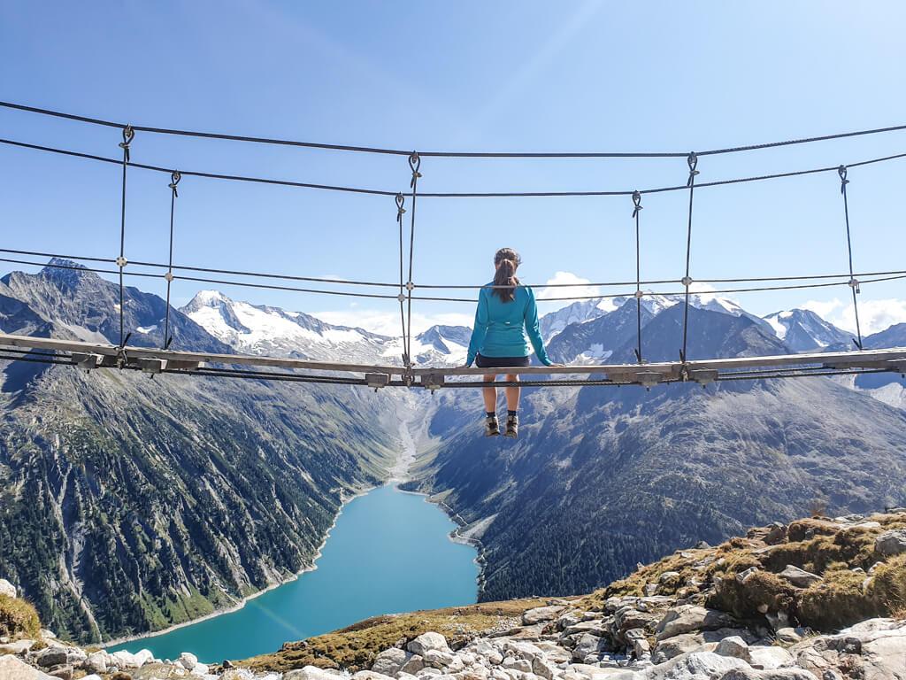 Frau sitzt auf einer Hängebrücke, die hoch über einem Stausee in den Bergen hängt. Der Stausee im Tal ist umgeben von schneebedeckten Bergen.