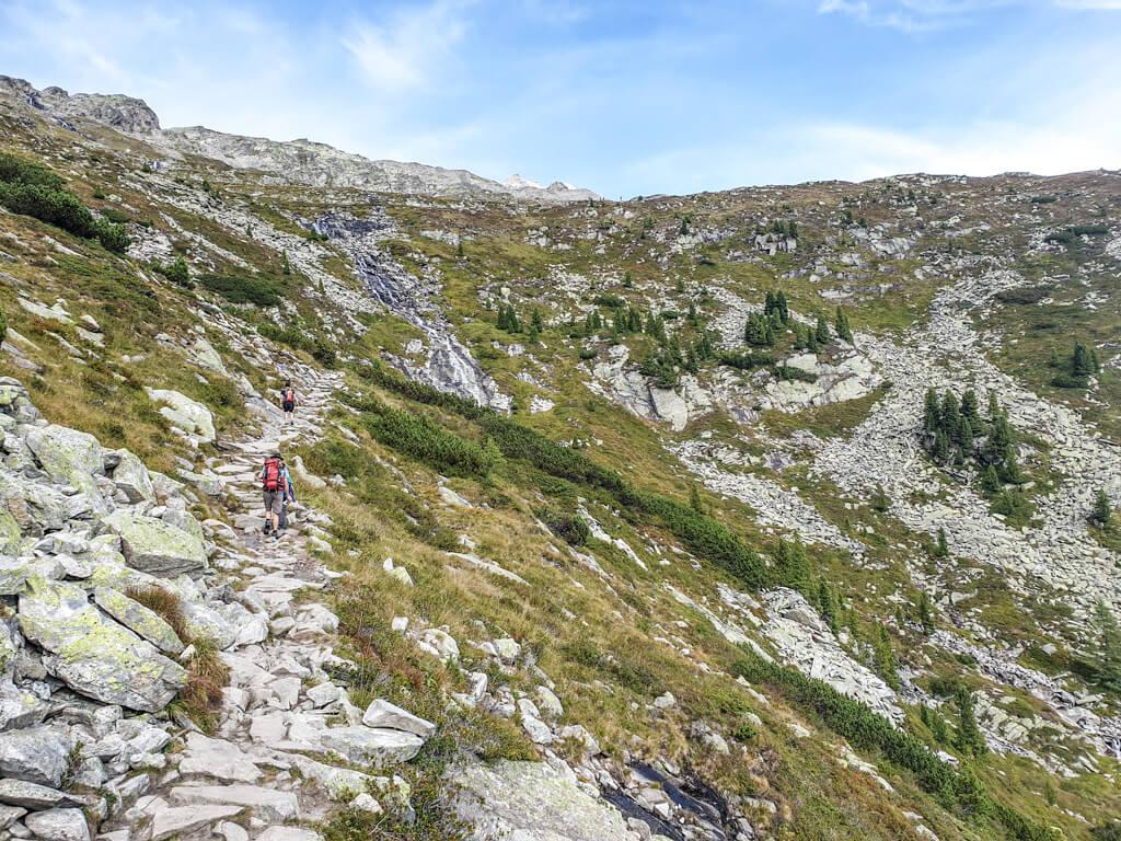 steiniger Wanderweg führt am Berg entlang, rechts vom Wanderweg liegen grüne Hügel mit weiteren Geröllfeldern und einem Wasserfall