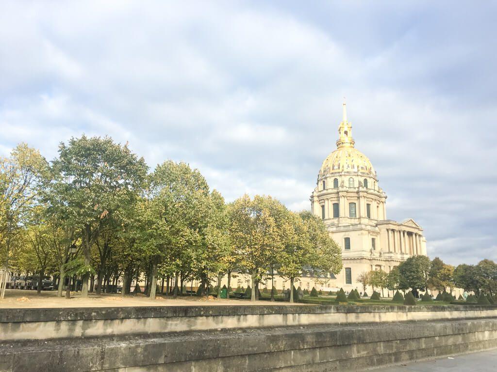 Invalidendom Paris - Straße mit grünen Laubbäumen, am Rande eine Kirche mit goldener Kuppel
