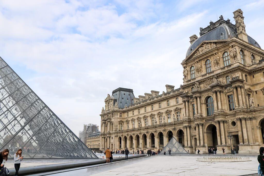rechts ein historisches Gebäude, links eine Glaspyramide