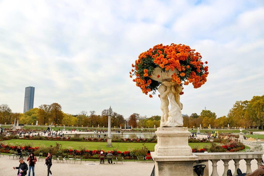 Statue mit bunten Blumen, dahinter eine Gartenanlage