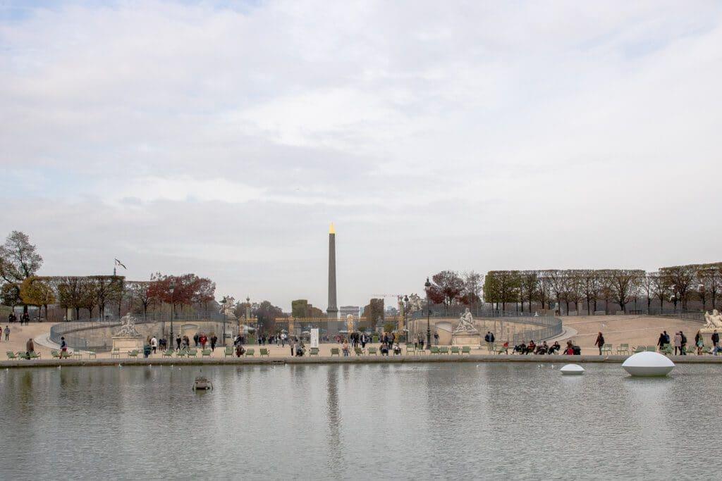 Teich mit Blick auf einen großen Platz mit einem Obelisken