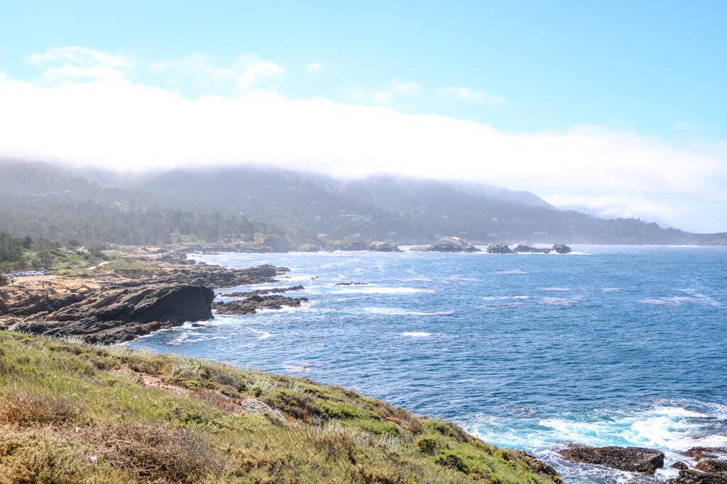 Blick aufs Meer mit leichten Wellen, die sich schäumend an Felsen in Ufernähe brechen. Am Ufer eine Küstenlinie mit Gräsern und Felsen