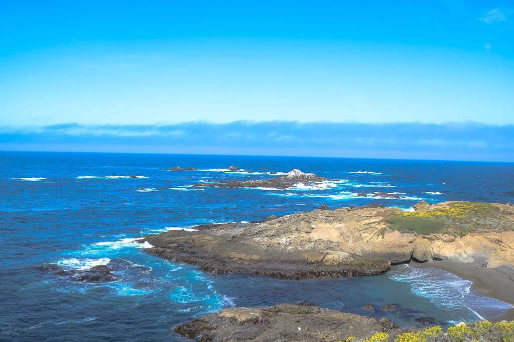 Monterey-Point Lobos - strahlend Blauer Himmel über dem Meer; Felsen im Meer vor der Küste