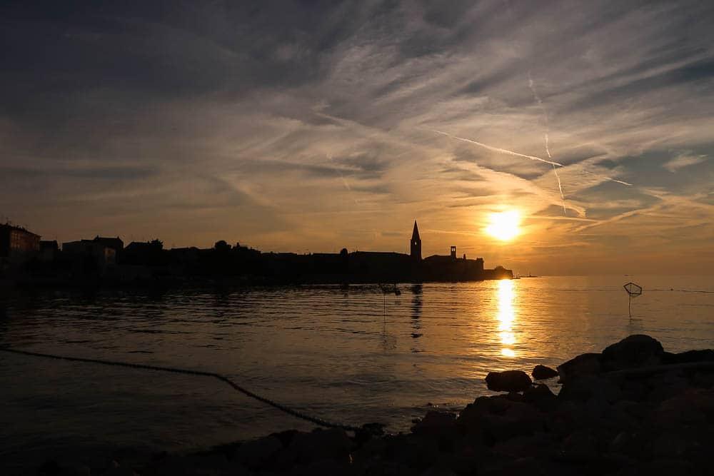 Sonnenuntergang über dem Meer mit Blick auf eine Stadt