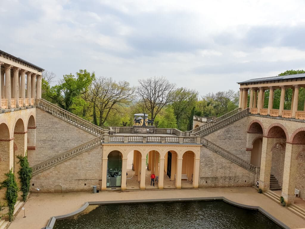Innenhof eines Schlosses mit Teich und Säulengängen
