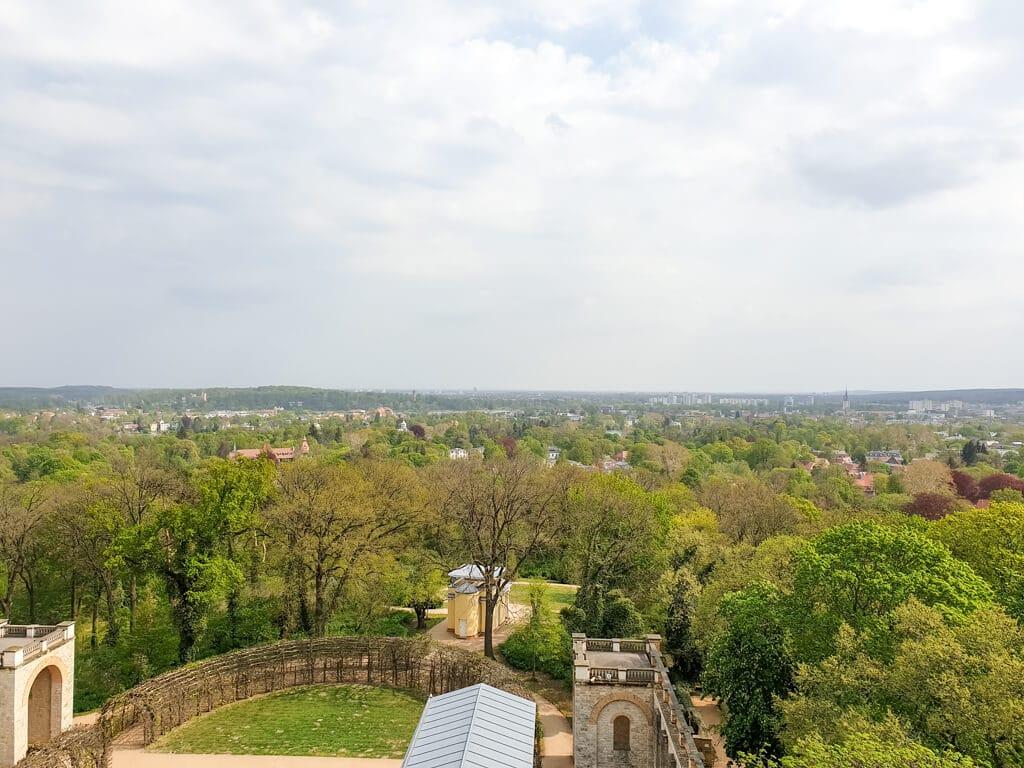 Ausblick vom Belvedere Pfingstberg über grüne Wälder und ein Schloss