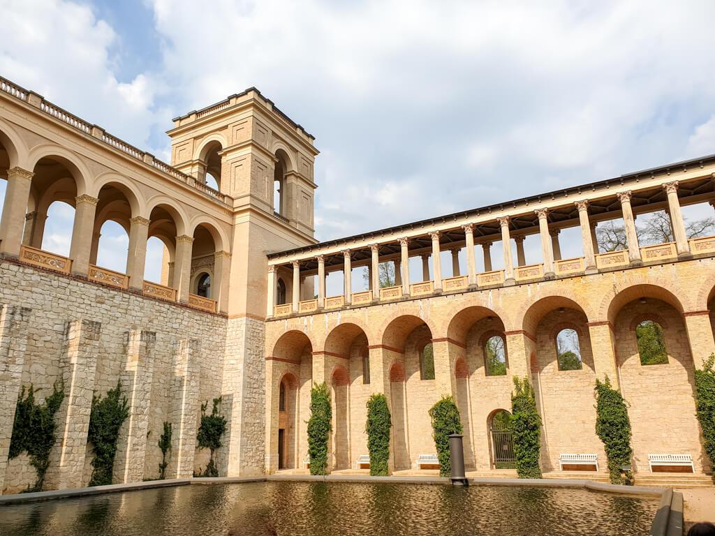 Innenhof eines Schlosses mit Säulengängen und einem See in der Mitte