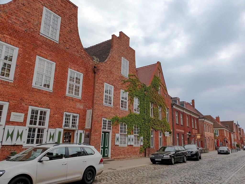 Backsteinhäuser in einer Reihe - daneben eine Straße mit Kopfsteinpflaster