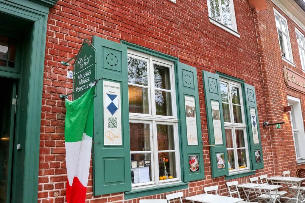 Backsteinhaus mit grünen Fensterläden und Sprosenfenstern