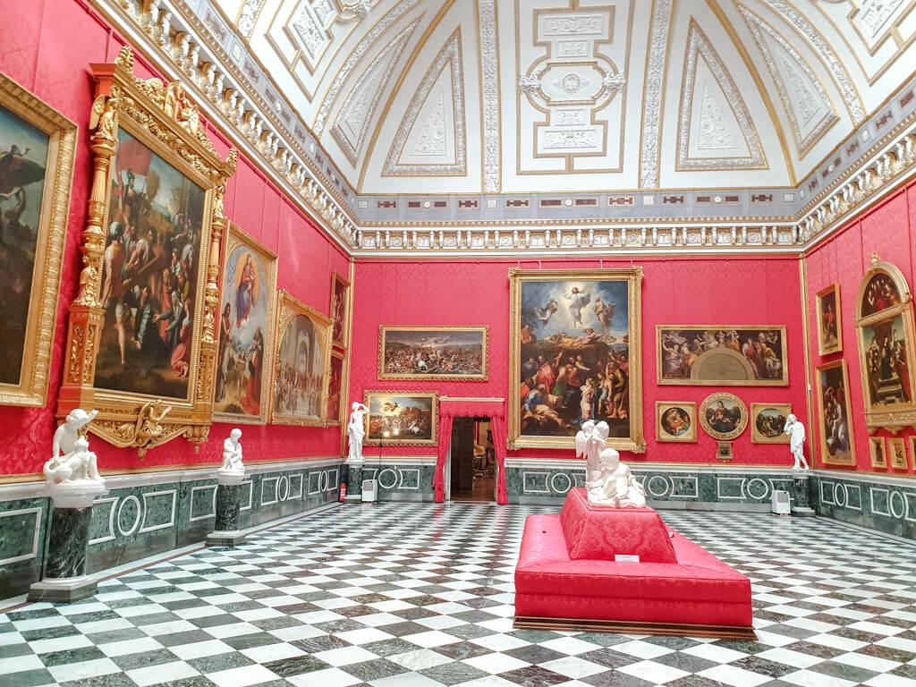 rot tapezierter Saal mit kariertem Marmorboden und hohen Decken - an den Wänden wertvolle Gemälde in goldenen Rahmen