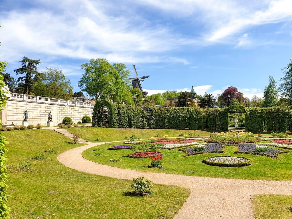 Rondell mit Blumenbeeten auf einer Rasenfläche - im Hintergrund eine Windmühle