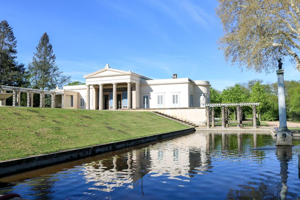 Schloss Charlottenhof Potsdam: Ein kleines Schloss spiegelt sich im Wasser eines Teiches