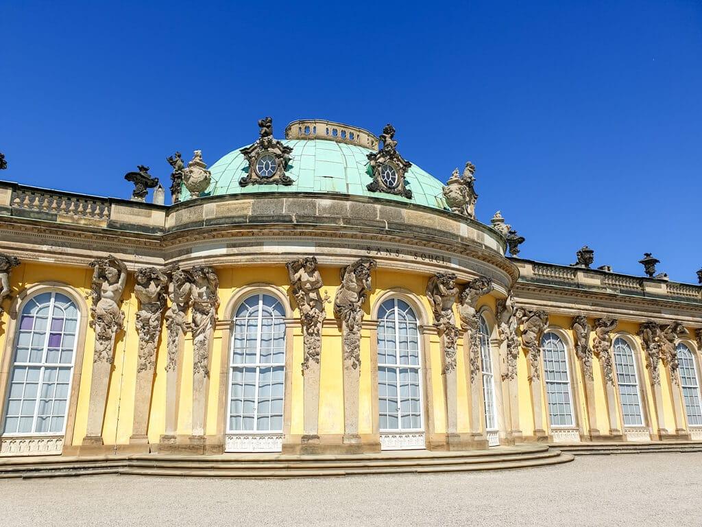 historisches Schloss mit gelbem Anstrich und Aufschrift Sans Souci