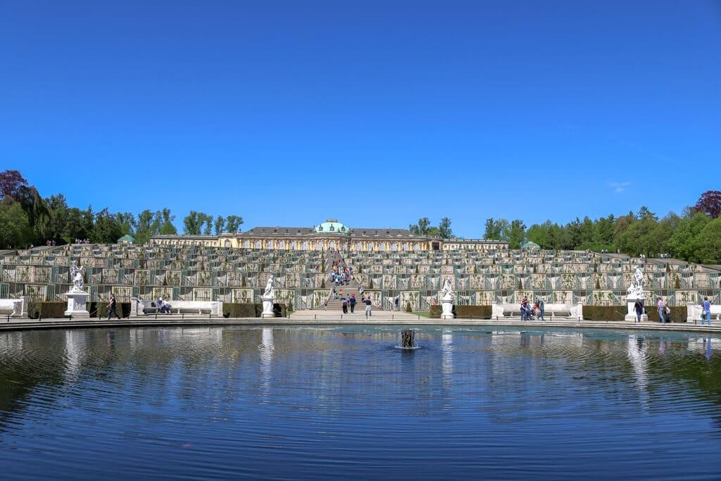 Schloss Sanssouci Potsdam: Im Vordergrund ein großer Teich - dahinter Stufenförmige Anordnung bis zu einem Schloss