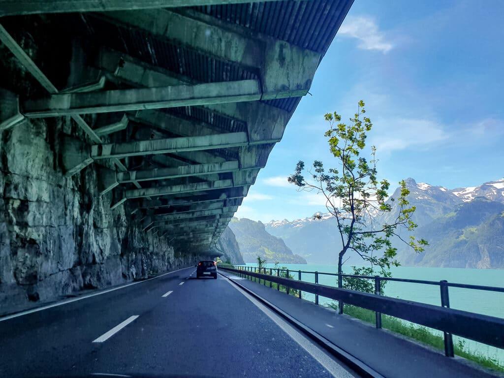 Straße unter einem Bergüberhang - rechts ein leuchtend blauer See