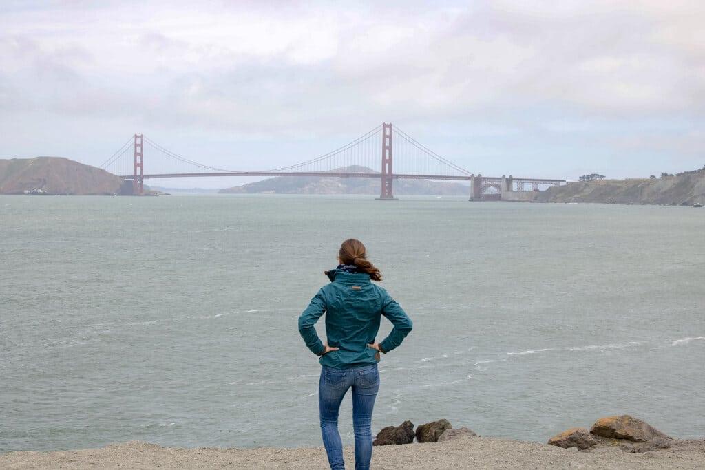 Frau schaut über das Meer zur Golden Gate Bridge