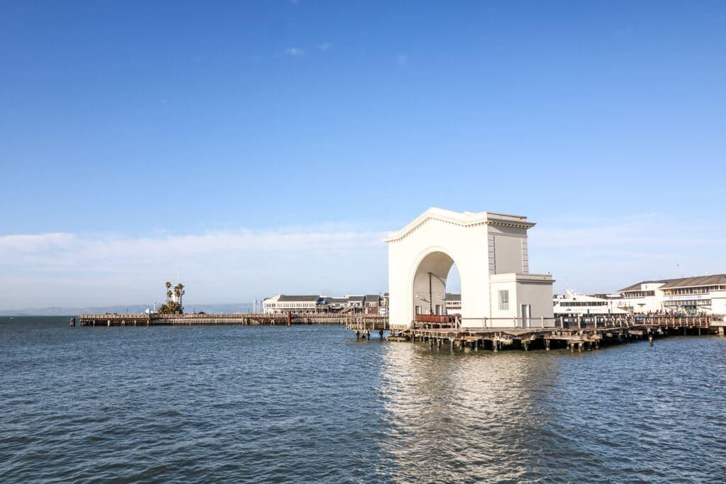 San Francisco Pier 43; Wasser in der Bucht von San Francisco mit Blick auf einen historischen, weißen Torbogen