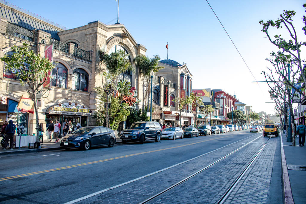 Straße mit einigen geparkten Autos und Geschäften und Restaurants an der linken Seite - Straße in Fishermans Wharf in San Francisco