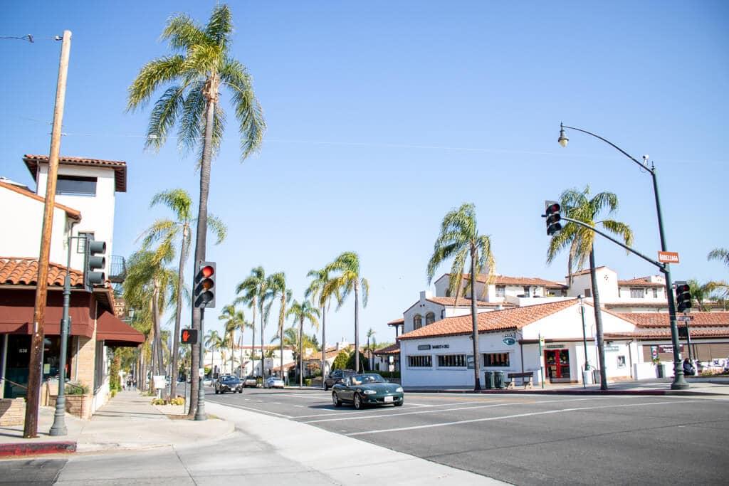Straße mit Palmen zu beiden Seiten und niedrigen weißen Gebäuden