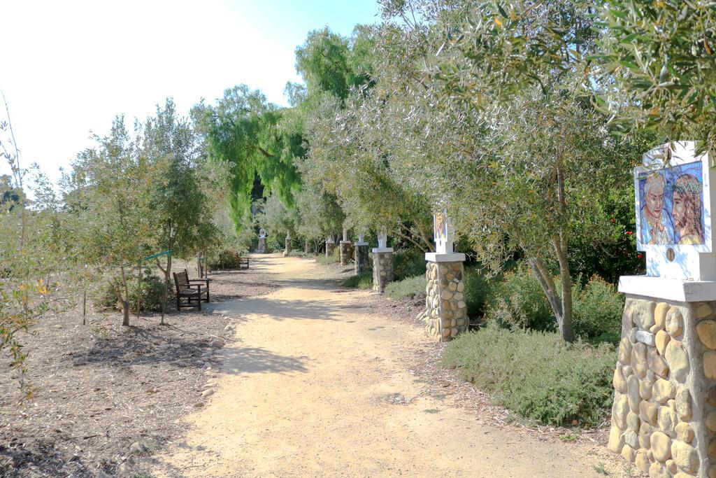 Weg durch einen Olivenhain - rechts stehen mehrere Stationen des Kreuzweg