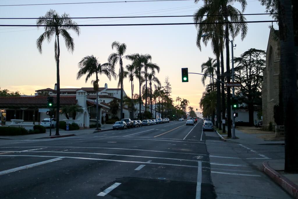 Sonnenuntergang über einer mit Palmen gesäumten Straße