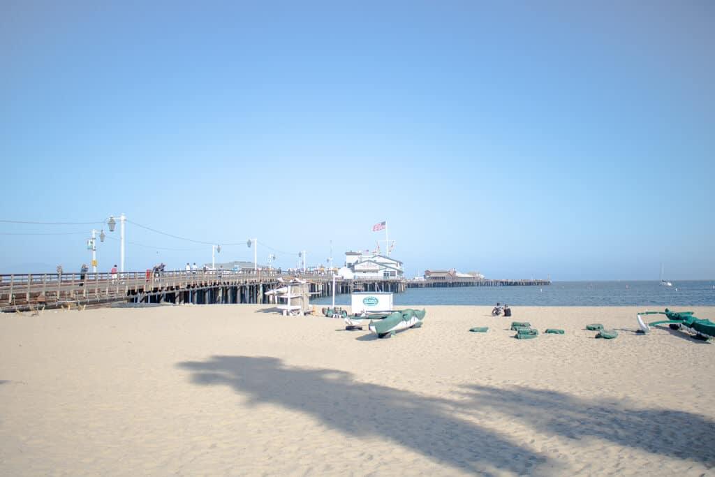 Strand mit wenigen Booten und einem Pier an der linken Seite