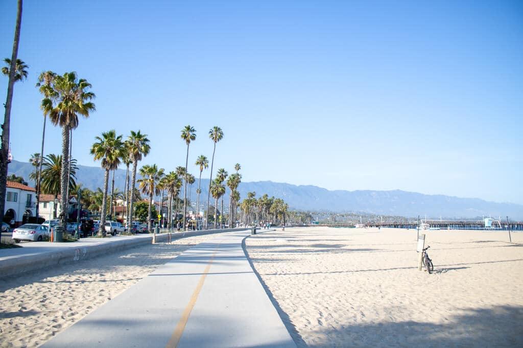 Strandpromenade auf einem breiten Sandstrand - links eine Straße mit Pamen