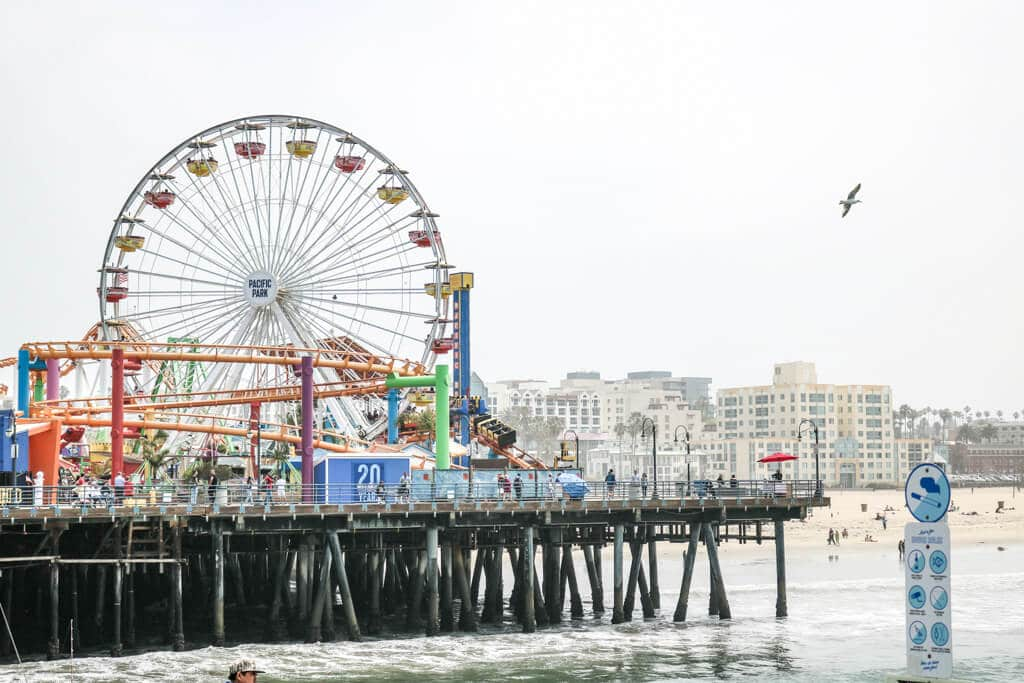 Santa Monica Pier / Pacific Park: Holzsteg im Meer mit Riesenrad und anderen Fahrgeschäften - dahinter der Strand und einige Häuser