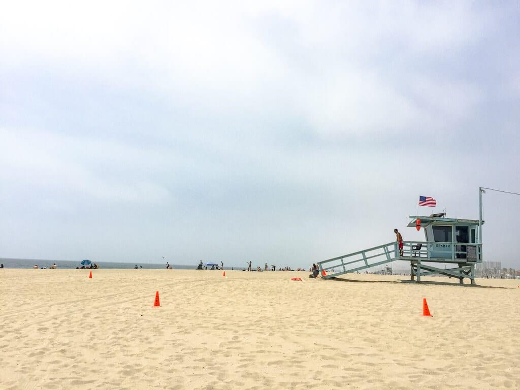 Strand mit hellblauem Bademeister-Häuschen und USA-Flagge