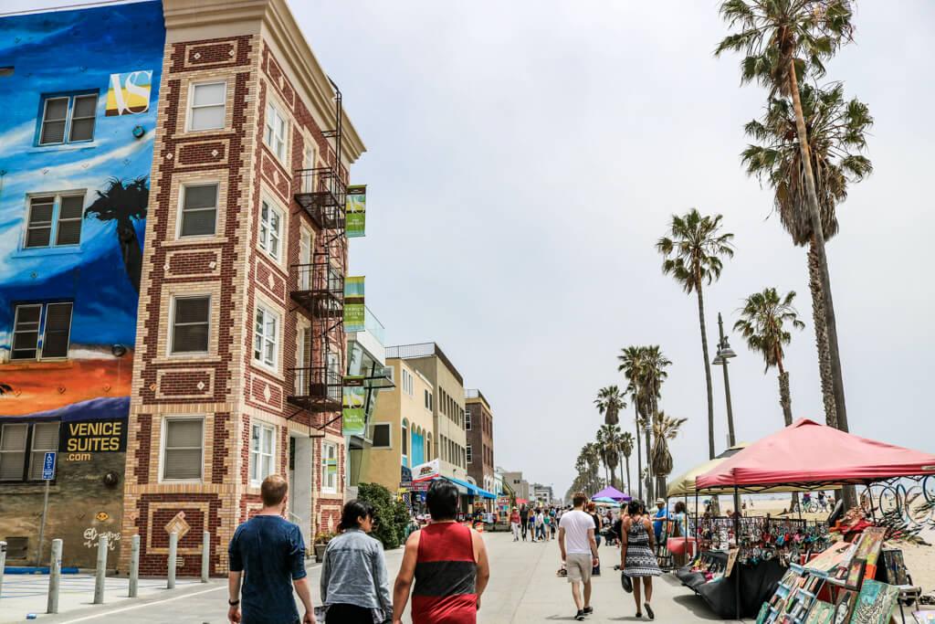 Weg mit Häusern auf der linken Seite, rechts verschiedene, kleine Stände, Palmen und der Strand