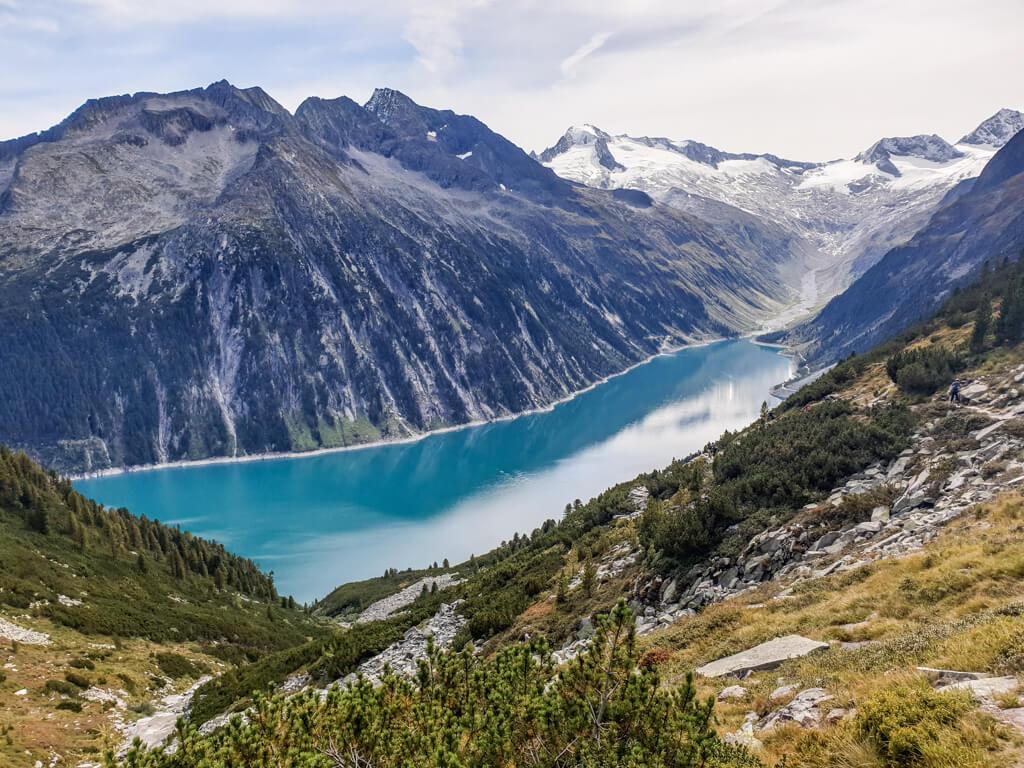 türkisblauer Bergsee umgeben von hohen Bergen, die im oberen Bereich schneebedeckt sind. Im Vordergrund fallen grüne Berghänge in Richtung See ab