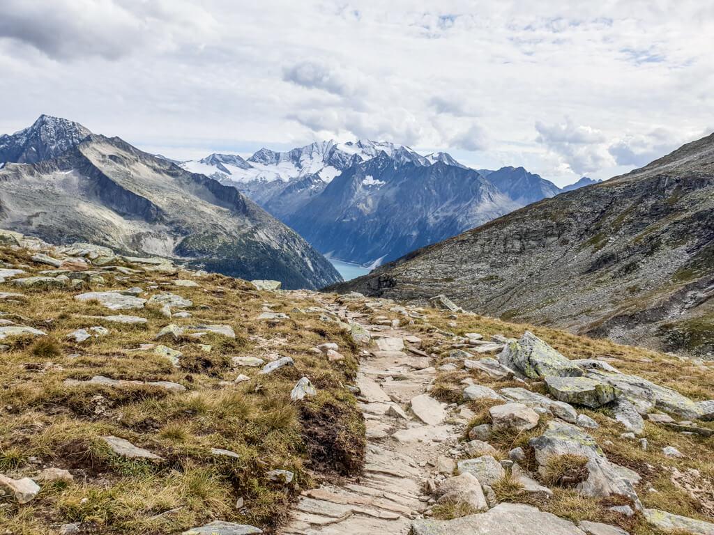 Bild zeigt einen steinigen Pfad auf einem Berg mit Gras und Blick auf einen Stausee darunter. Der See ist an der Rückseite von schneebedeckten Bergen umgeben