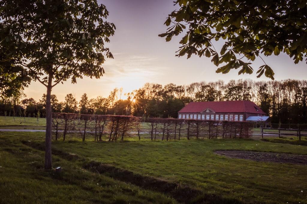 Blick über Wiesen und Felder zur Orangerie am Schloss Nordkirchen bei Sonnenuntergang