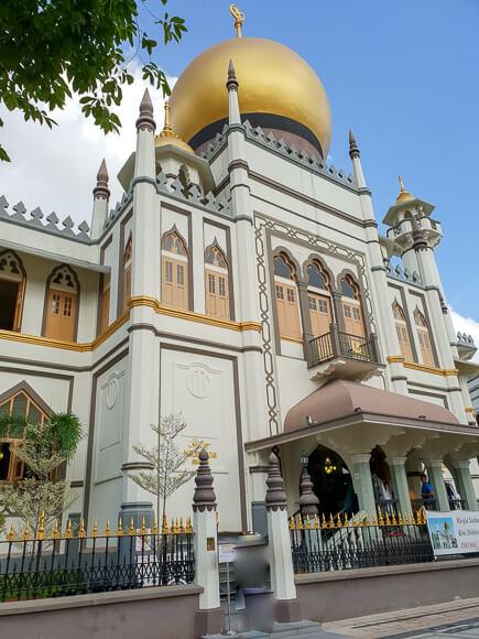 Moschee aus weißem Stein mit goldener Kuppel und goldenen Elementen