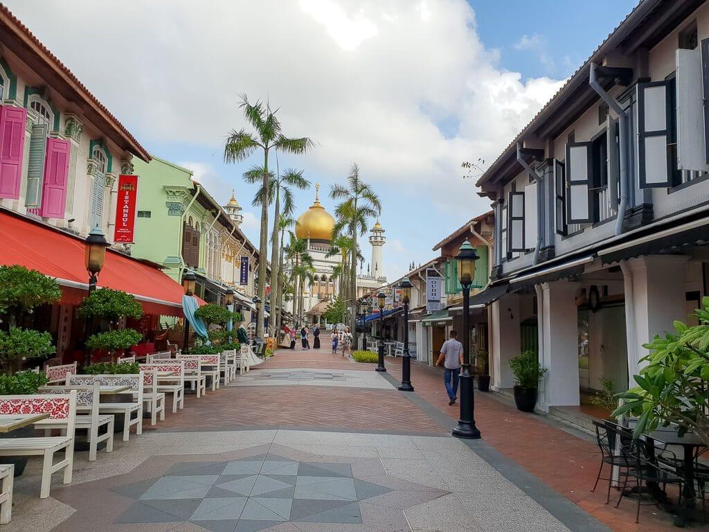 Fußgängerzone mit Gebäuden auf beiden Seiten - am Ende der Straße Palmen und die goldene Kuppel einer Moschee